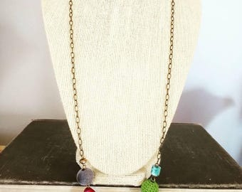 Long beaded necklace in cool colors on an antiqued brass chain.