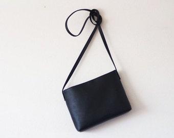 Minimalist black leather crossbody bag with magnetic closure
