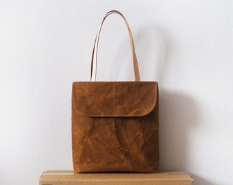 Waxed canvas tote bag with front flap and tan leather handles