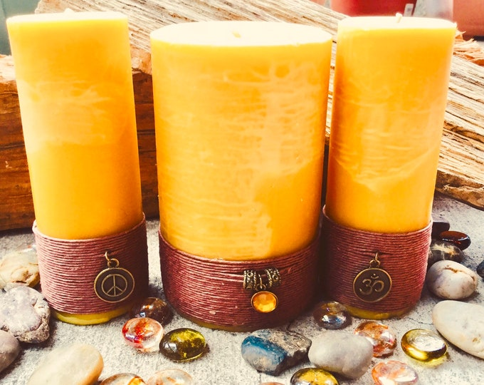 """Set of 3 100% pure beeswax pillar candles spiritual gift set, wrapped and charmed with an Om and Peace charm. 2-2""""x 5"""" and 1-3""""x 5"""" pillars"""