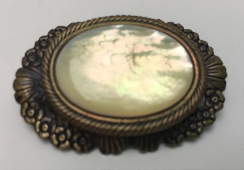 Oval shaped Victorian style mother of pearl brooch. Mid century mother of pearl brooch in an ornate antiqued gold setting