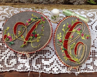 Monogram brooch embroidered on cotton tulle, with pearls, silk ribbons, mouliné yarns and finished with antique lace