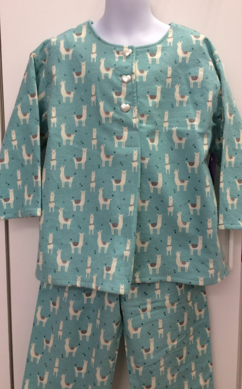 Two piece pajama set front pleat and elastic waist bottoms. Gray and white llamas on a soft turquoise flannel background Long sleeves