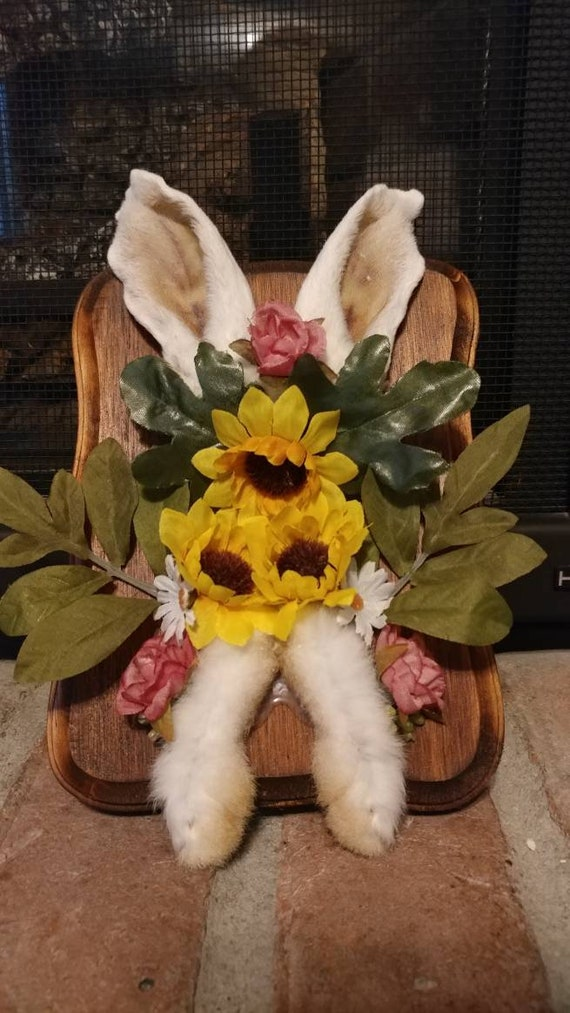 Black rabbit foot mounted plaque with artificial flower