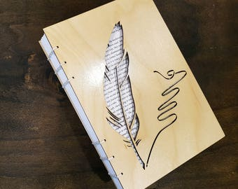Notebook with quill cut out on wooden cover. Bound with Coptic Stitching.
