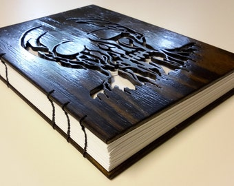 Notebook with melting skull on dark wood cover - scrollsaw cutout