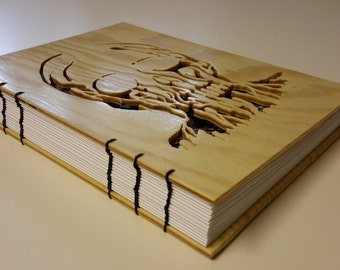 Notebook with melting skull on light wood cover - scrollsaw cutout