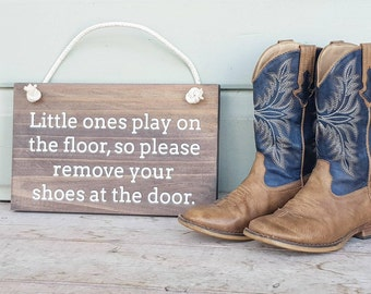Little ones play on the floor, so please remove your shoes at the door Painted Wood Sign - Stained Timber White Text
