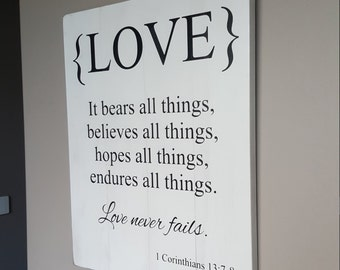 LOVE bears, believes, hopes, endures all things. Love never fails 1 Corinthians 13:7,8 - Distressed White with Black Text Wooden Rustic Sign