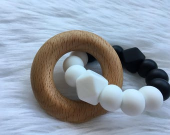 Monochrome black and white silicone teether with organic wooden beech ring. Baby teething toy in neutral colours.