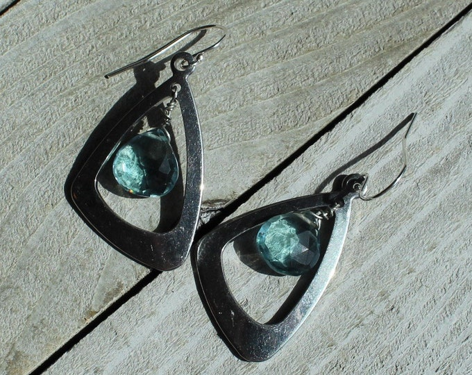 Faceted polished aquamarine suspended inside stainless steel triangle shapes on 925 sterling silver ear wires