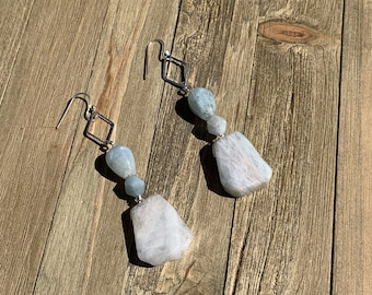 Raw aquamarine stones suspended from silver diamond shapes, hanging from 925 sterling silver earwires