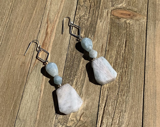 Raw aquamarine suspended from silver diamond shaped finding on 925 sterling silver ear wires