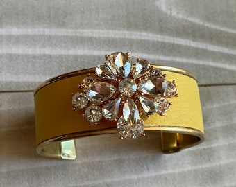 Clear rhinestone set in rose gold color metal set on yellow leather inlaid in brass cuff bracelet, adjustable