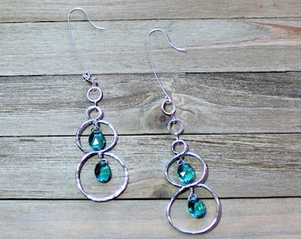 Brilliant teal blue peacock quartz briolettes suspended inside silver figure 8 with silver circles on sterling silver earwires