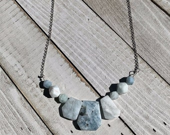 Raw aquamarine pendant with silver oval geometric shapes on silver chain
