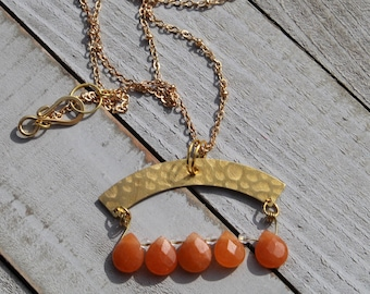 Red faceted aventurine beads with arched shaped brass bar on a gold colored satellite chain