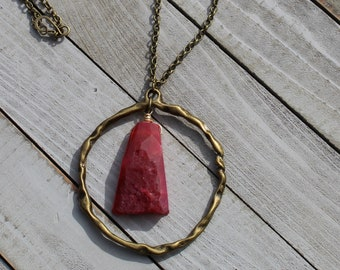 Large red and pink rough agate stone suspended inside from large brass circle on gold chain
