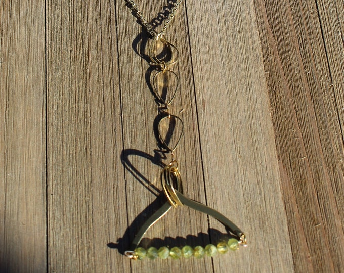 Semi-precious birthstone peridot beads suspended from brass arch and teardrop shapes with peridot beads on gold chain
