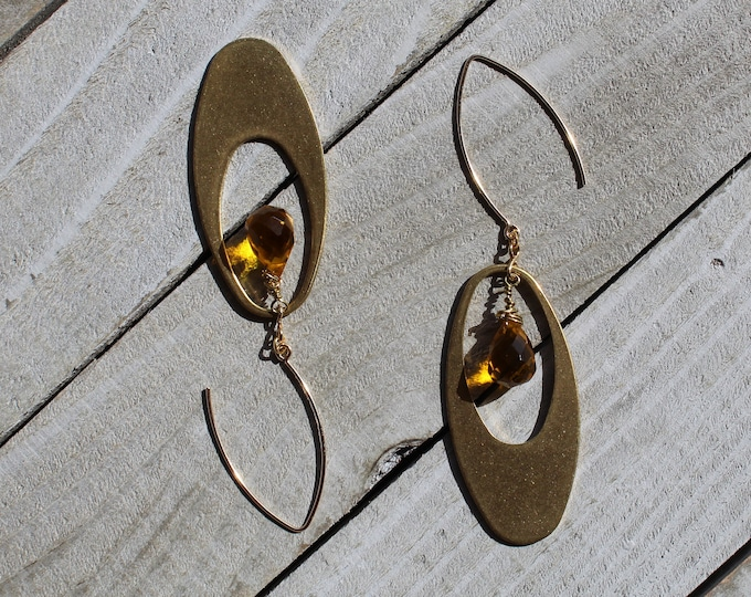 Faceted citrine stone, suspended inside brass oval and hanging from 14k gold filled earwires