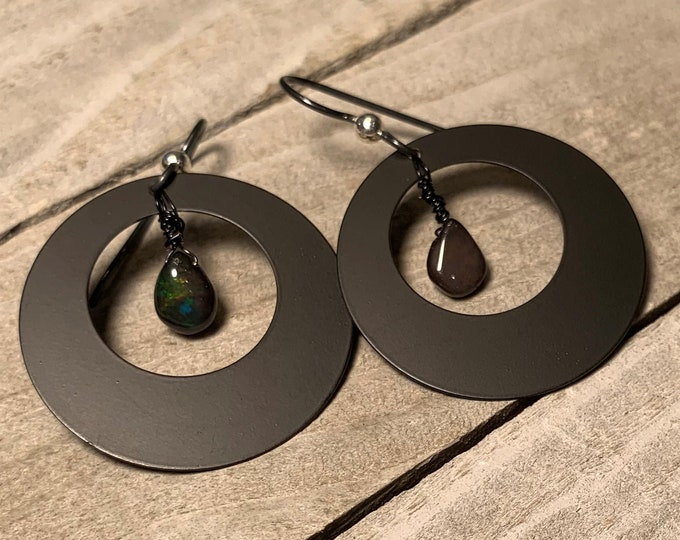 Welo black opal briolettes suspended inside matte black circle shapes on nickel free black niobium ear wires