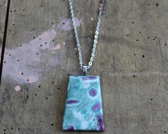 Ruby in fuschite rectangle slab pendant with decorative silver accents on a silver toned chain