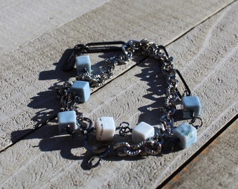 Double wrap bracelet with square cut blue opal stones on gunmetal chain with oval shapes and closes with s hook