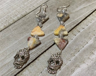 Crazy lace agate triangle shaped stones with white topaz and silver rhinestone skulls, hanging from 925 sterling silver twisted earwires