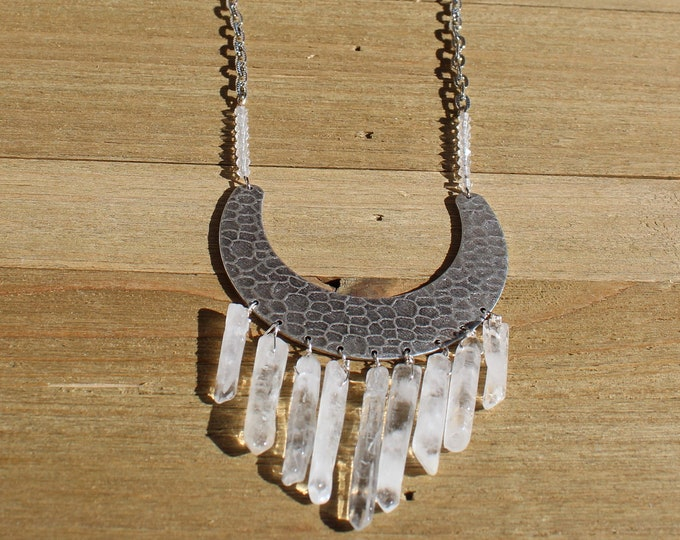 Hammered silver crescent pendant with clear quartz stones suspended from it with natural white topaz accents on a cut silver chain