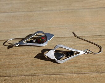 Welo black opal briolettes suspended inside stainless steel teardrop silver shapes on 925 sterling silver ear wires