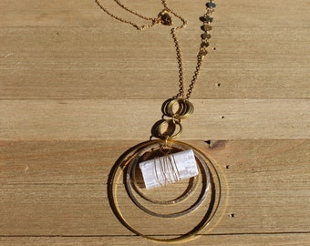 Wrapped raw frosted white selenite suspended inside brass circles on long brass chain with accents and lobster clasp close