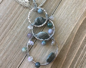 Hand made circular pendant with various green agate beads threaded throughout, long chain