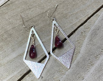 Ruby polished briolettes inside stainless steel kite shaped finding, hanging from 925 sterling silver earwires