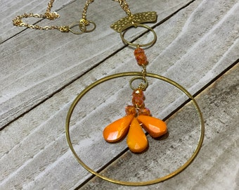 Faceted orange coral teardrops with czech glass beads hand wired to copper circle suspended on gold colored chain