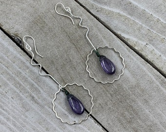 Polished color changing alexandrite suspended inside silver wavy circle shapes in 925 sterling silver ear wires