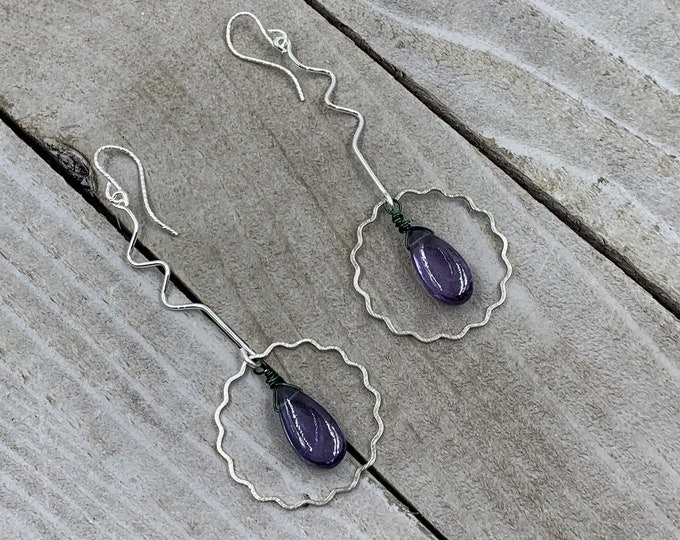 Featured listing image: Polished color changing alexandrite suspended inside silver wavy circle shapes in 925 sterling silver ear wires