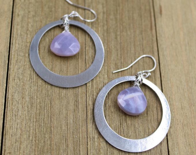 Faceted polished Oregon Blue Boulder Opal suspended inside silver circle shapes on 925 sterling silver ear wires