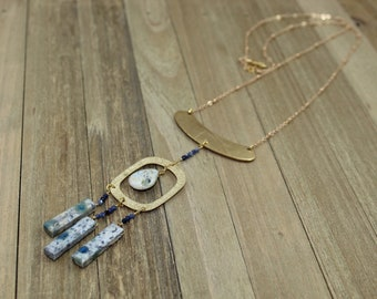 K2 Jasper and sapphire beads suspended from oval shaped brass on gold colored chain with s hook closure