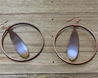 Orange chalcedony elongated teardrop stones suspended inside copper circles, and hanging from 14k rose gold filled french hooks