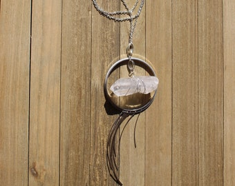 Wrapped raw clear quartz inside silver circles with silver fringe on long silver chain with lobster clasp close