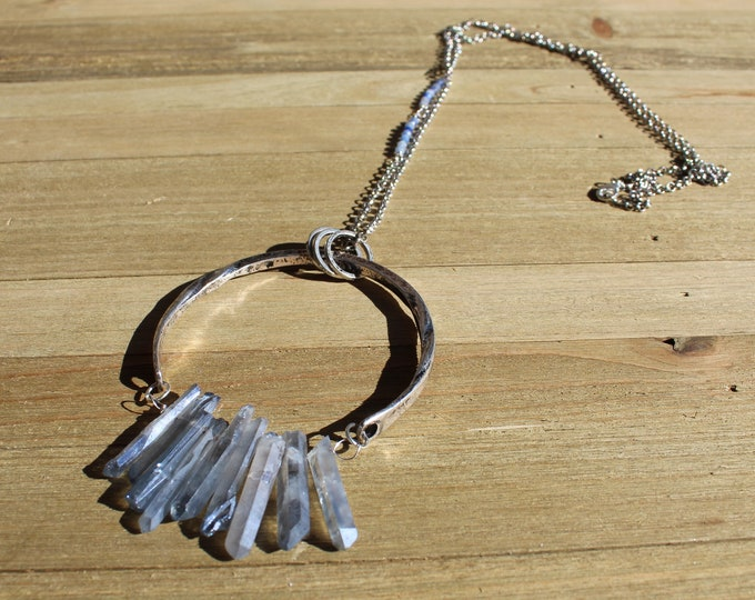 Frosted blue quartz stick beads suspended inside from large 3/4 silver circle on accented silver chain with dumortirite bead accents
