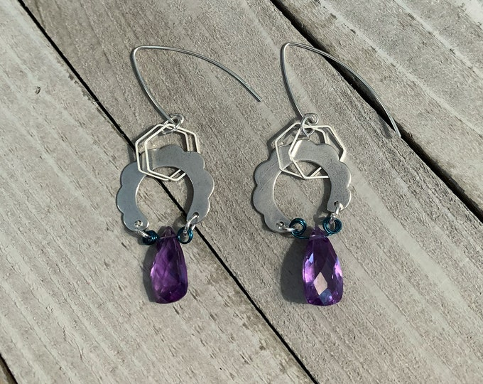 Polished color changing alexandrite suspended under silver wavy half circle shapes in 925 sterling silver ear wires