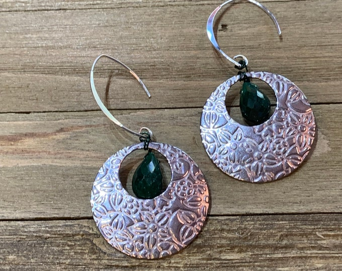 Faceted polished emerald suspended inside stainless steel circle shapes with embossed flowers on 925 sterling silver ear wires