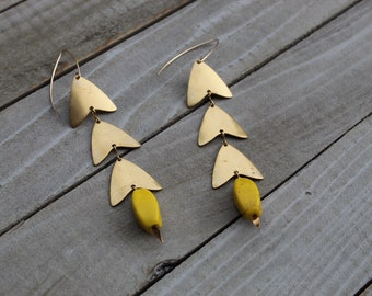 Yellow dyed magnesite beads suspended from chevron brass findings, attached to 14k gold filled earwires