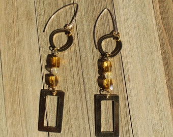 Citrine, brass and rutilated quartz stones in between rounded squares and rectangle shapes, hanging from 14k gold filled earwires