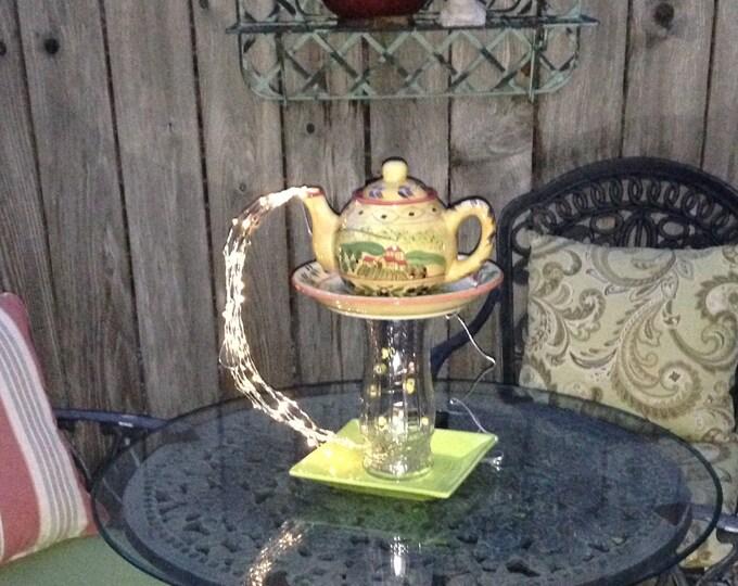 Yard art lighted teapot tower teapot table center piece glass repurposed yellow teapot green plate lighted teapot tower beaded copper spiral