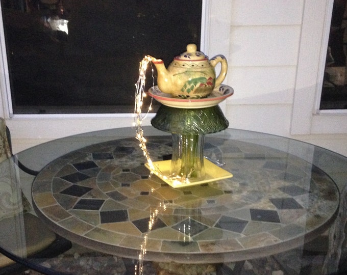 Yard art lighted teapot tower teapot table center piece glass repurposed yellow teapot square plate lighted teapot tower green etched glass