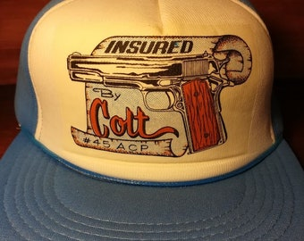 d33af4cd4aa Vintage Insured by Colt 45 blue and white snapback trucker hat