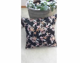 Black pillow with pastel colored leaves
