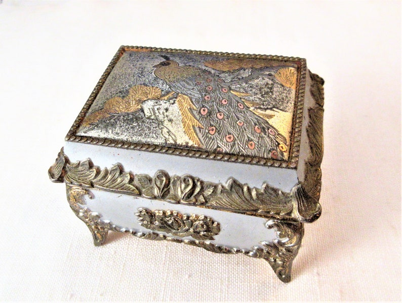Good used condition Multi tone metal with a hinged lid and gold velvet lining the top depicts a peacock in a tree Small Jewelry Box
